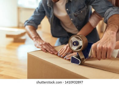Young couple packing boxes and moving into their new home
