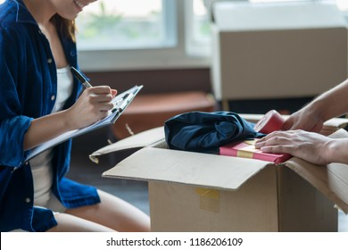 Young couple packing and checking stuff by using checklist before moving to new residence.