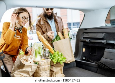 Young couple packing shopping bags with fresh food into the car trunk, view from the vehicle interior