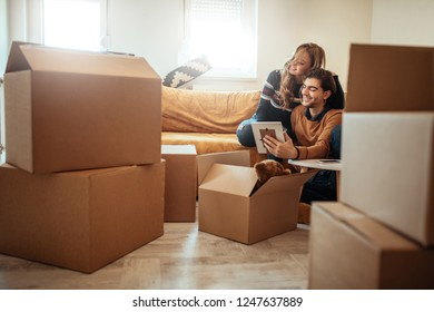 Young couple packing stuffs in cardboard boxes for moving into new apartment