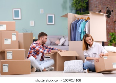 Young couple packing wardrobe boxes on moving day