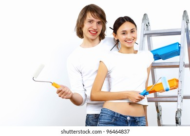 Young couple with paint brushes doing renovation together