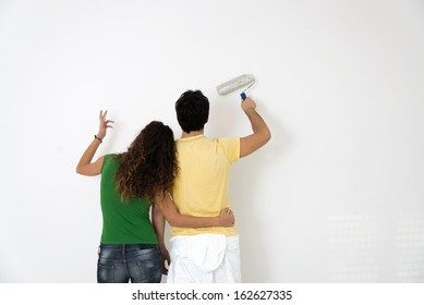 young couple paint a room