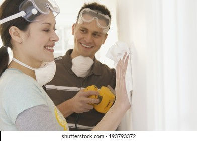 Young Couple Painting The Wall In The Apartment