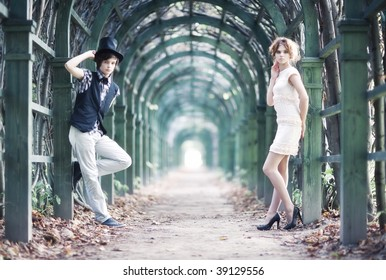 Young couple in a park with long passage.