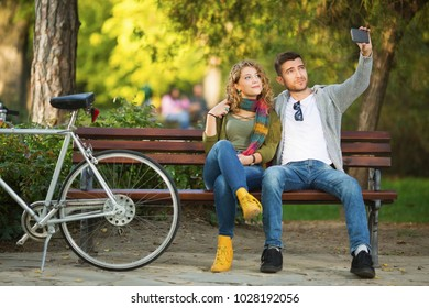 Young couple in park making selfies