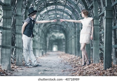 Young couple in a park stretching hands. Shallow dof effect.