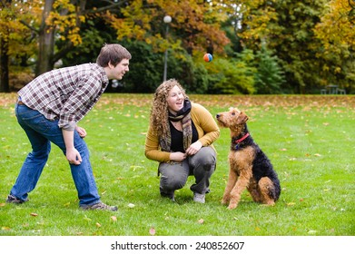 Young couple in a park with their dog.