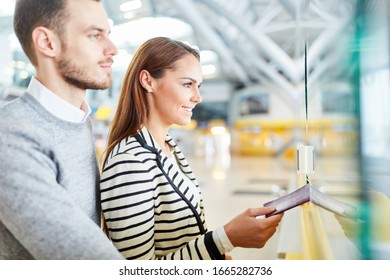 Young couple with passport at check in counter in airport terminal at entry