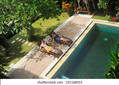 young couple of people relax on villa by swimming pool
