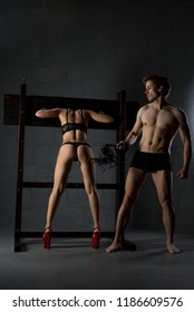 Young couple perfoming erotic bdsm play shot