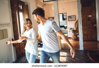 Young couple performing dance and having fun in living room of modern apartment.