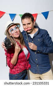 Young couple in a Photo Booth party holding fake paper mustache
