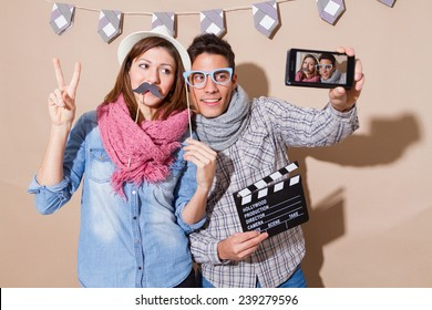 Young couple in a Photo Booth party with gesture face  taking selfie,
