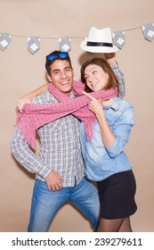 Young couple in a Photo Booth party with gesture face