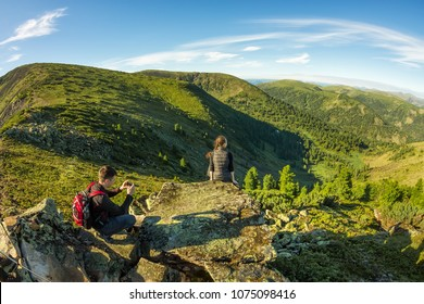 young couple photographed on a rock in the mountains view