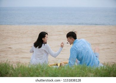 Young couple picnicking by the sea.