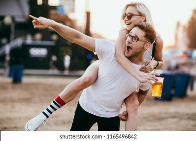 Young couple piggy backing at music festival