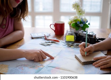 Young couple planning honeymoon vacation trip with map.