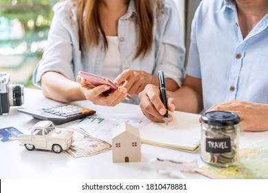 Young couple is planning and managing home expenses (house, car, travel, and credit card) together at home