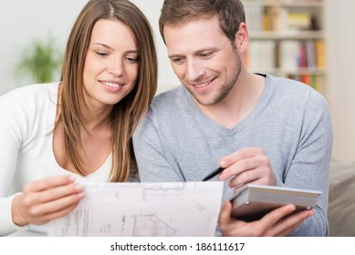 Young couple planning a new purchase sitting together pointing to a document held by the wife as the husband does the necessary calculations on a calculator