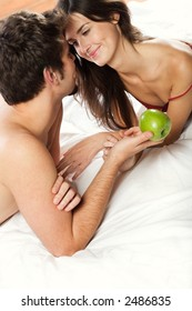 Young couple playing with apple on the bed in bedroom