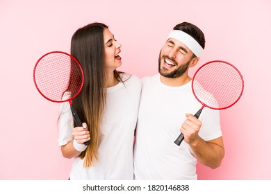 Young couple playing badminton isolated laughing and having fun.