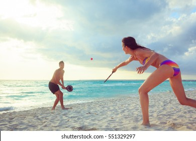 Young Couple Playing Beach Tennis