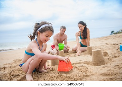 A young couple is playing at the beach with their daughter, a six year old is building a sand castle with her parents. Focus on the girl