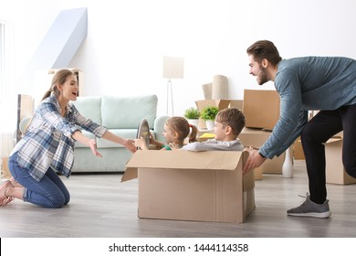 Young couple playing with children indoors. Happy family on moving day