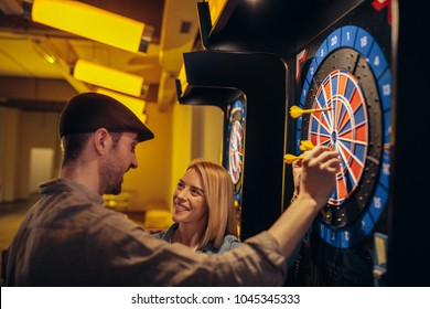 Young couple playing darts