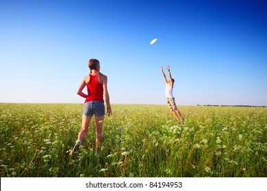 Young couple playing with disc on a green meadow with grass on clear blue sky background. Focus on a woman