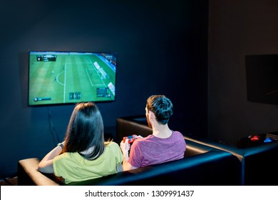 Young couple playing football game with playstation sitting on the couch at the playing club, back view with tv screen