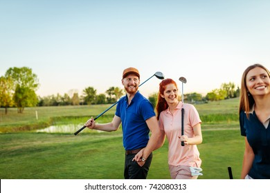 Young couple playing golf together on the course.