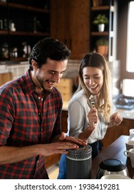 Young couple playing with kitchen utensils. Boyfriend and girlfriend having fun while preparing food