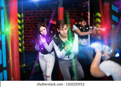 Young couple playing laser tag with friends in labyrinth illuminated by bright beams of laser guns