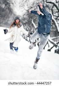 Young couple playing outdoors. Winter season.