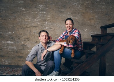 Young couple playing with their puppy. The concept of a happy family life.