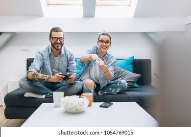 Young couple playing video games at home.