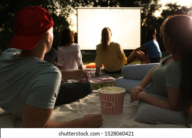 Young couple with popcorn watching movie in open air cinema. Space for text