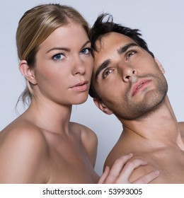young couple portrait naked in studio on isolated grey background