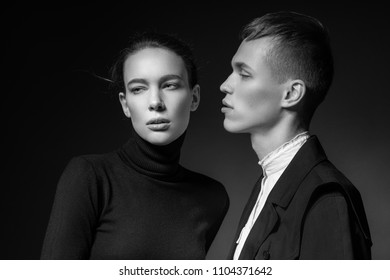 Young couple posing on dark background