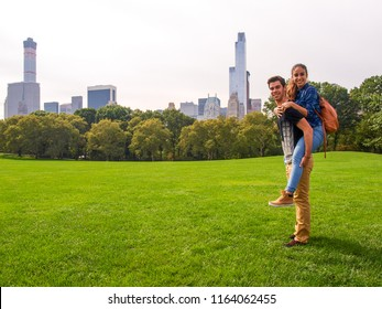 A young couple posing at Sheep Meadow in Central Park, NY, New York, USA.