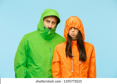 The young couple posing at studio in autumn jacket isolated on blue. Human negative emotions. Concept of the cold weather. Female and male fashion concepts