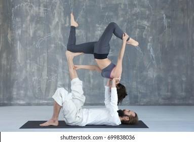 Young couple practicing yoga on floor