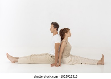 Young couple practicing yoga, sitting back to back indoors on white abstract polygon background. Young caucasian woman and man smiling and meditating together in acroyoga pose in tantra school. Full