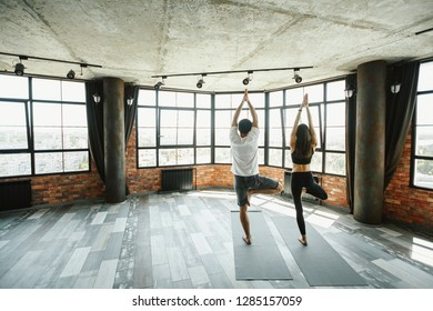 Young couple practicing yoga together, doing Vrikshasana, Tree pose. Yoga together concept, copy space