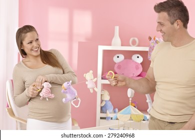 Young couple preparing baby's room, having fun.