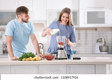 Young couple preparing delicious milk shake in kitchen
