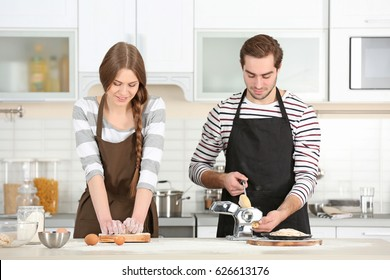 Young couple preparing pasta on kitchen table